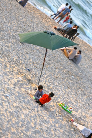 Children on the beach under a green umbrella