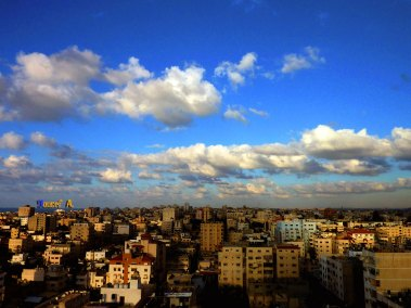 Gaza cityscape from a high window on a sunny day with white fluffy clouds