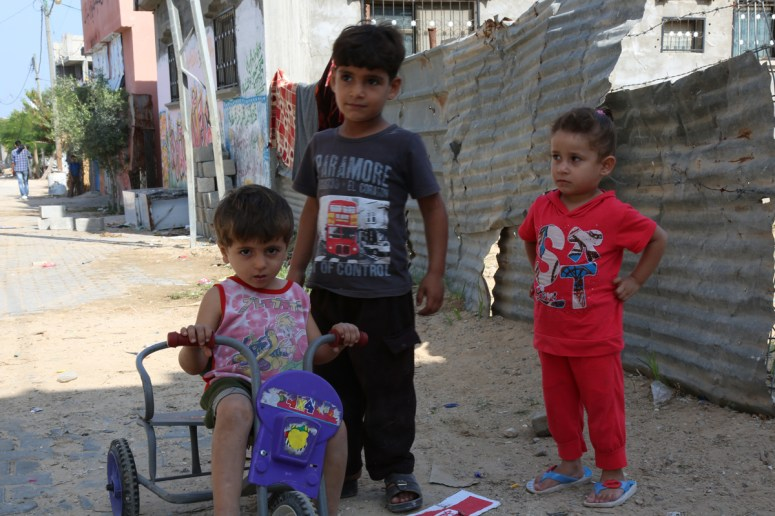Small boy on a trycle and two other children