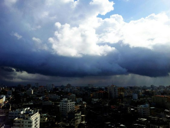 Gaza from a high window under a heavy dark cloud