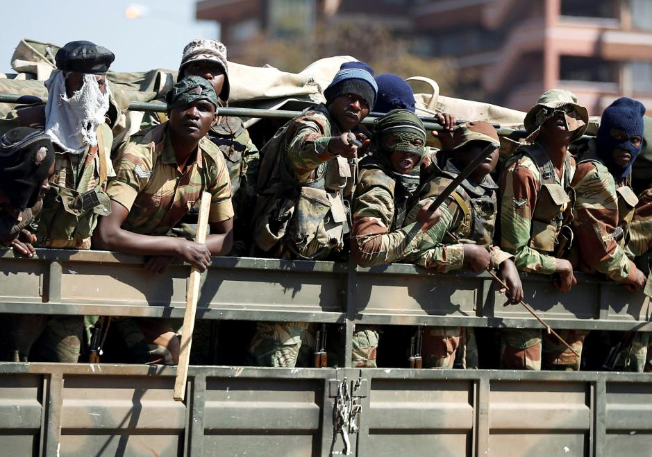 Members of the military gesture to the photographer as they patrol the streets of the capital Harare
