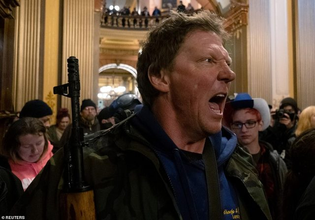 27860734-8275171-A_protester_is_seen_yelling_at_Michigan_State_Police_while_holdi-a-116_1588283688689-640x448