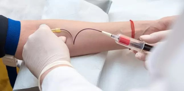 Doctor hands sticking needle into female vein for blood sampling