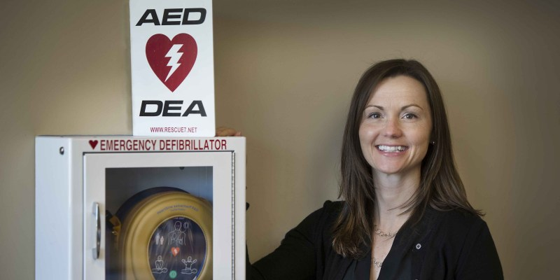 Amy Butt, co-chair of the University Centre OHS Committee, stands beside the AED located in the Student Health Centre