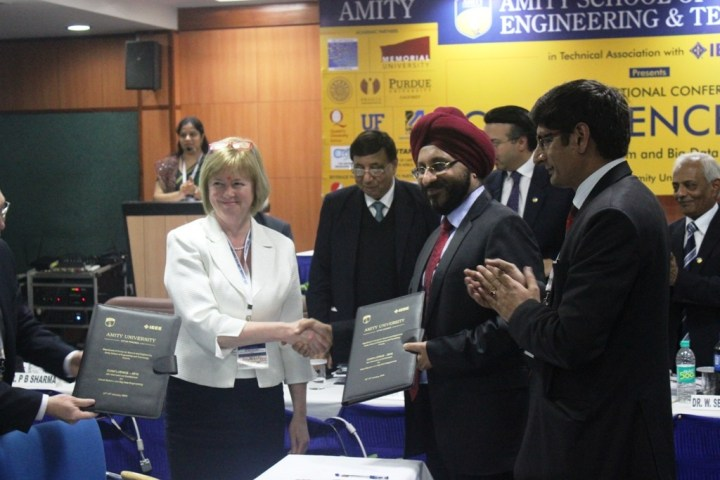 At left, Sonja Knutson signs a memorandum of understanding with Amity University.