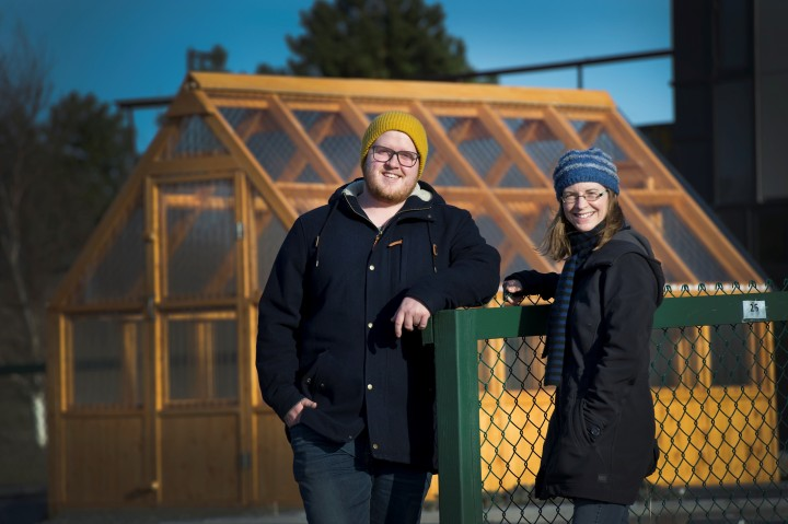 Master's history student Ethan Doney and Toby Rowe, sustainability co-ordinator, in front of the community garden's new greenhouse.