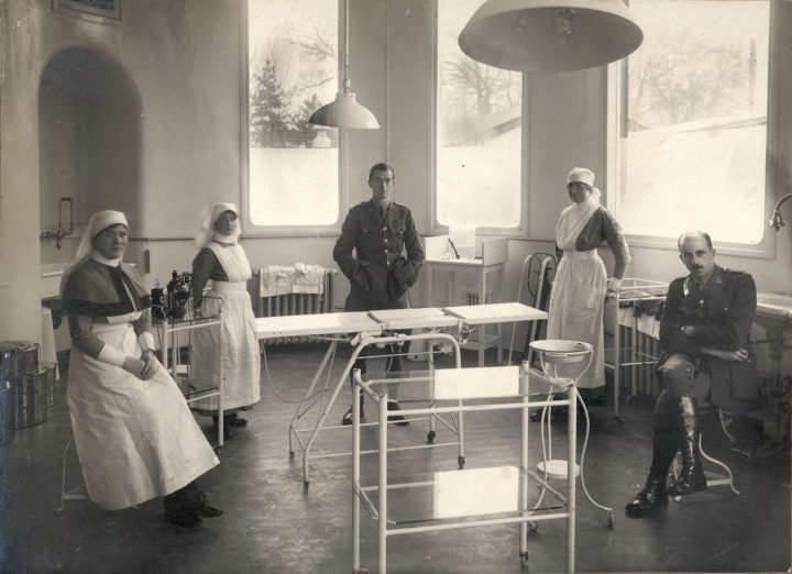 The plastic surgery operating room in 1917 at Queen's Hospital, Sidcup, England. Seated to the right is Harold Gillies (surgeon); standing at centre is Rubens Wade (anesthesiologist).