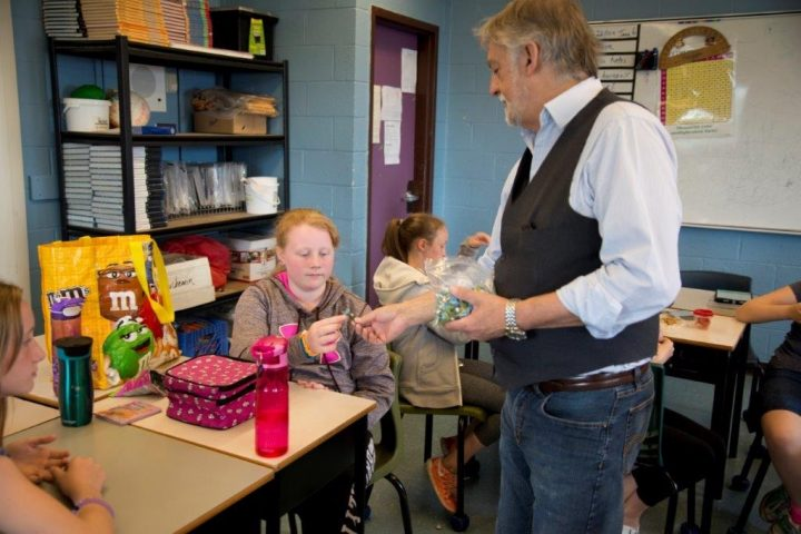 Prof. Fred Hawksley giving out forget-me-not pins to students at St. Edward's Elementary School in Kelligrews.