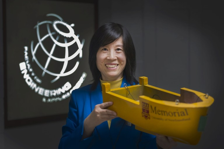 Dr. Heather Peng holds a fishing vessel model made by Memorial's Department of Technical Services, a unit within the Office of the Vice-President (Research).