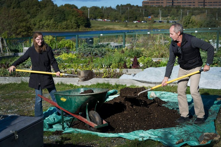 From left, Toby Rowe and Tim Walsh shovel compost at the community garden.