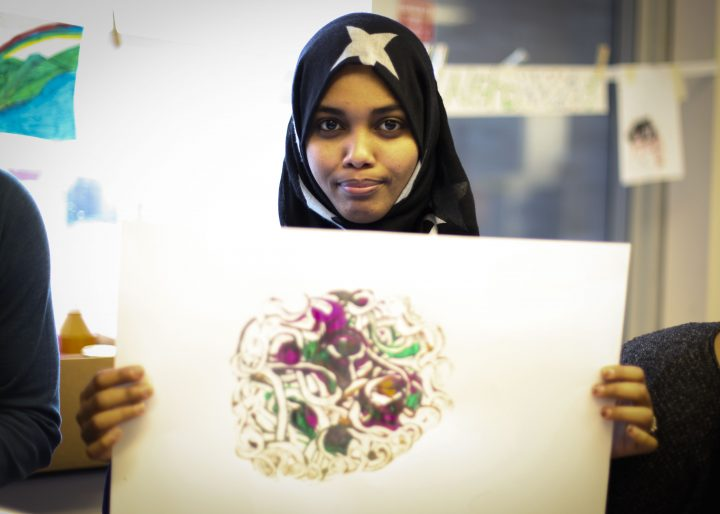 Aisha Hamid holds up her creation from the art hive.