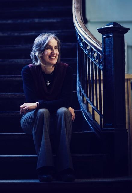 Dr. Dorothy Vaandering sits on the stairs at Bishop Feild School