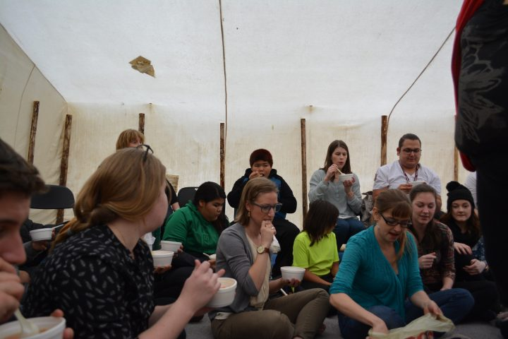 A group of students eating lunch in a canvas tent