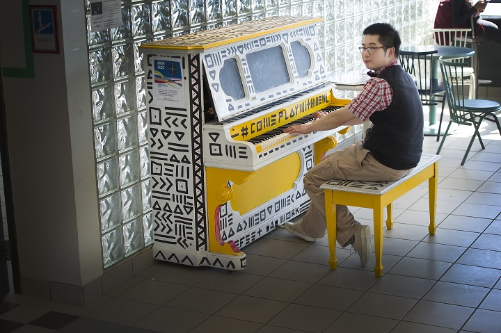 Michael So plays the piano in the University Centre.
