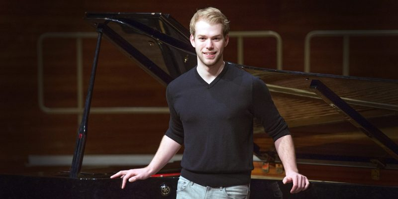 New School of Music graduate leans against a piano in Cook Recital Hall.