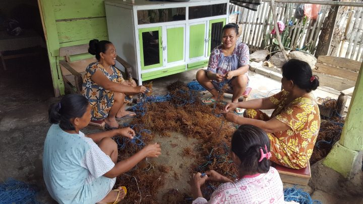 Women aquaculture producers tie seedlings to lines for seaweed farms in Bantaeng, Indonesia.
