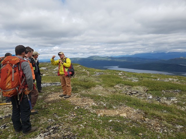 Dr. Stephen Piercey (yellow jacket) talks to colleagues about the geology around the Kudz Ze Kayah VMS deposits, Finlayson Lake region, Yukon, summer 2017