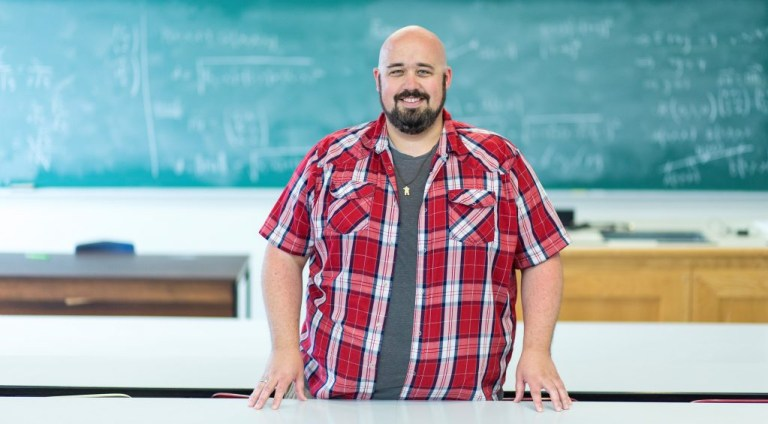 Jason Hatt stands in front of an empty classroom, with a blackboard in the background.