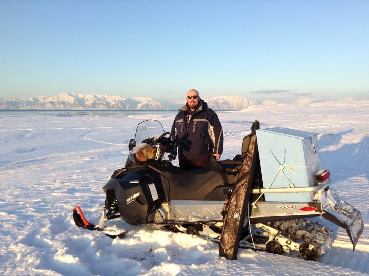 Jason Hatt poses with his skidoo with the mountains of Bylot Island in the background.
