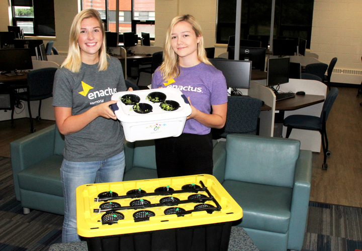 Emma Coady, left, and Taylor Young hold the new mini Project Sucseed unit available from Enactus Memorial. The original 12-pod unit is in the foreground.