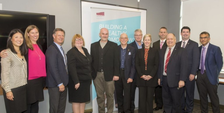A group of people representing Janssen Inc, Memorial University, Government of Newfoundland and Labrador and the community involved in the announcement stand at the front of a room