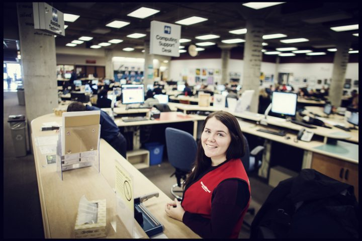 A young woman with a red vest stands behind the counter smiling.