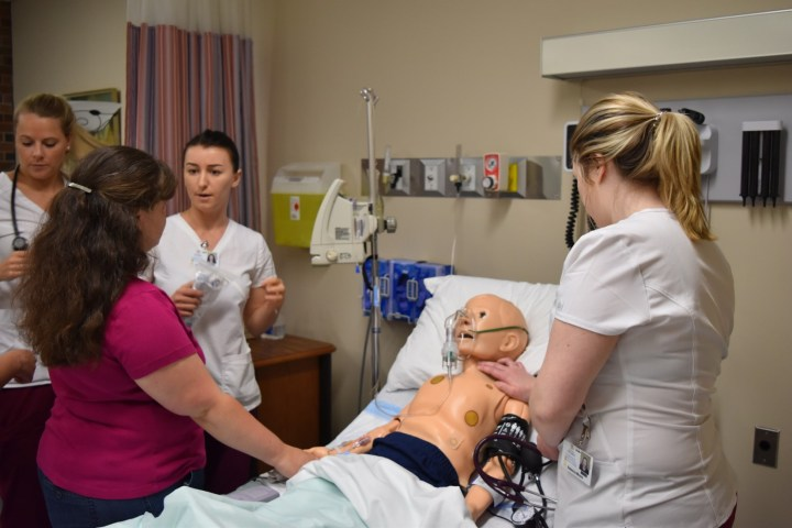 Three Nursing students work with their instructor as they care for a young patient in the simulation room