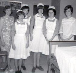 Old black and white photo of four female nursing students in cpas with dressed and white uniforms, and two nursing instructors