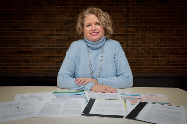 Faculty of Nursing professor Dr. Anne Kearney sits at a table surrounded by her published articles about breast screening