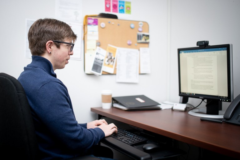 Ben Gould sitting as his office desk typing on his computer