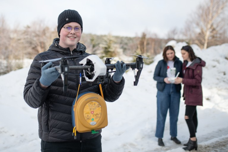 Enactus Memorial president Stephen Browne holds a drone that's carrying an AED. Enactus members Robyn Budgell and Hannah Blundon are in the background holding the remote control.