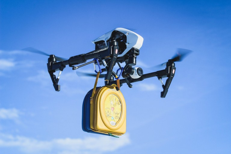 A drone in the air carries an automated external defibrillators, or AED.