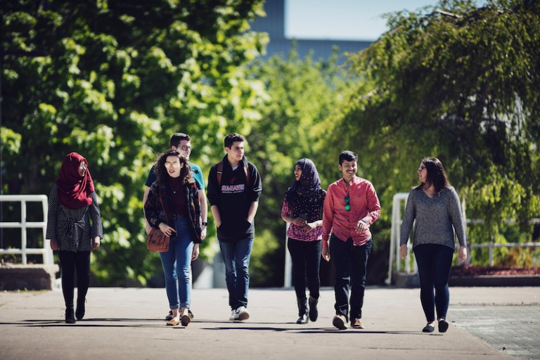 A group of students of varying ethnic backgrounds walk in a line on campus in summer