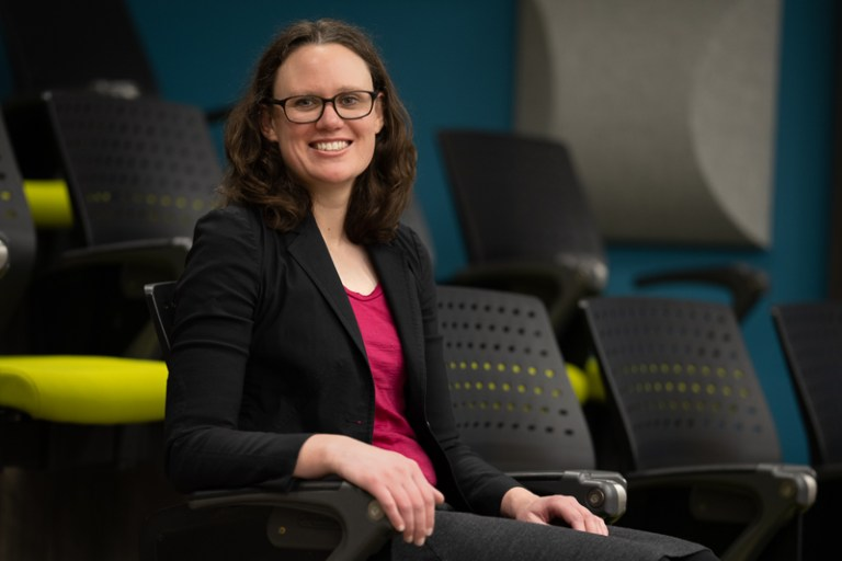 A woman with a black jacket, pink shirt, glasses and brown hair sits in a lecture theatre