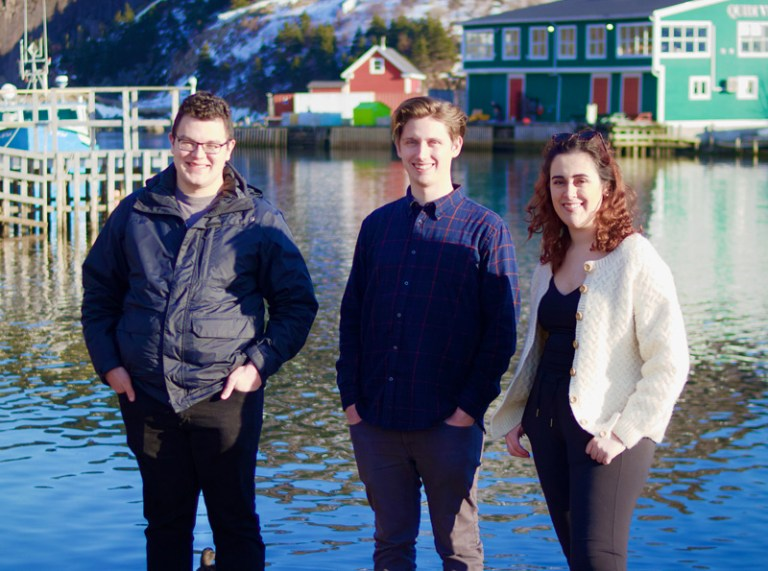 Three people smile at the camera while standing in front of Quidi Vidi Brewery in the Gut.