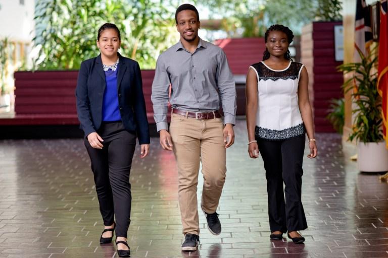 Three international students walk towards the camera while smiling