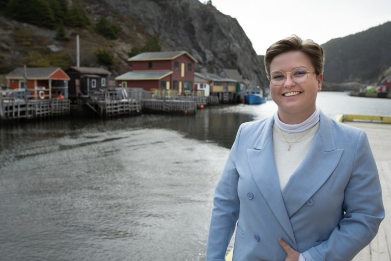 A woman with short brown hair and glasses wearing a light blue blazer stands in front of Quidi Vidi gut