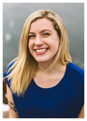 Kristen Murray has blond hair and wears a blue shirt.