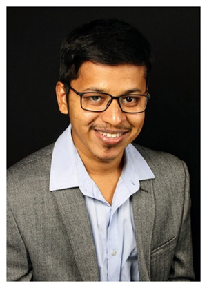 Pragadeesh Ravichandran wears glasses and a white collared shirt with a grey jacket.