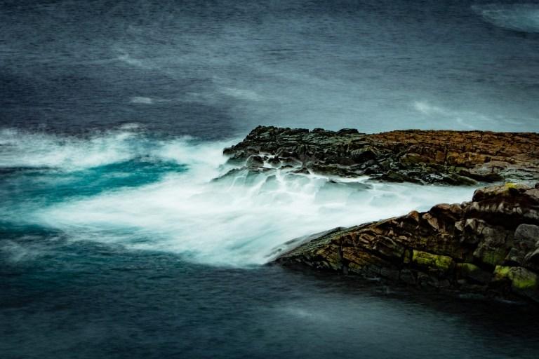 A large wave strikes a rocky outcrop in a dark blue ocean.