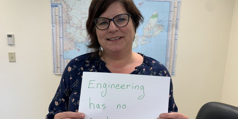"""A woman with brown hair and glasses and blue shirt with white flowers holds a sign that says """"Engineering has no gender."""""""