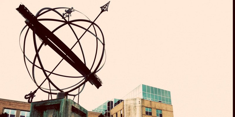A globe-like sculpture with arrows through it is pictured in front of the Arts annex on the St. John's campus.