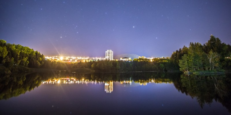The city of Corner Brook is visible in the far distance at night, with a pond in front and forest on either side. The lights of the city are reflected in the water.