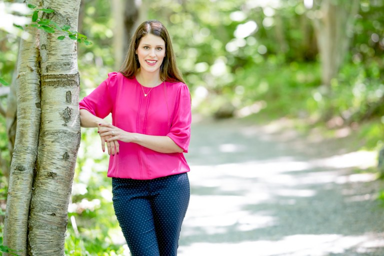 Dr. Gillian Morrissey is wearing a bright pink top. She leans against a birch tree on a wooded path.