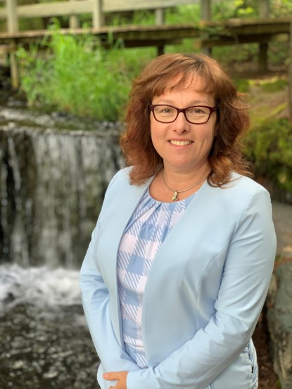 A woman dressed in a blue checkered shirt and cardigan is standing in front of a waterfall
