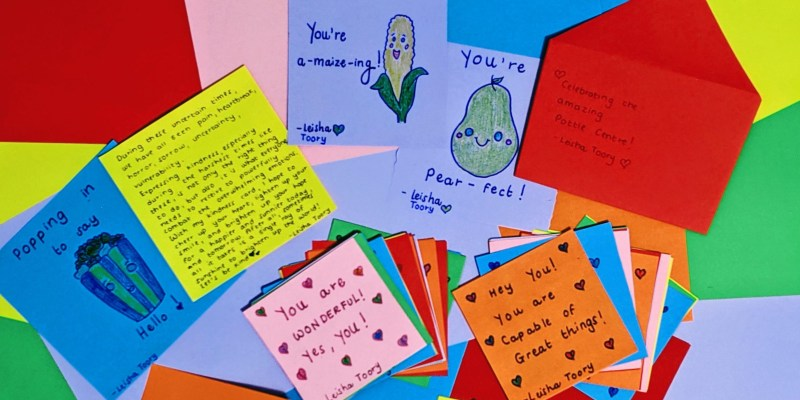 A number of handmade cards of different colours lie on top of each other with different sentiments written on them.