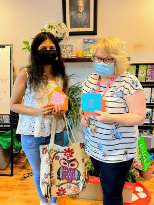 A woman with long black hair wearing a white shirt and jeans holding a cloth embroidered bag stands next to a woman with a blonde bob and wearing a striped shirt and black pants. Both are wearing masks and holding handmade cards.