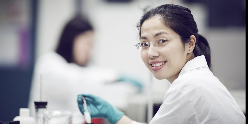 A woman with black hair and glasses wears a lab coat and works with a test tube in a laboratory.