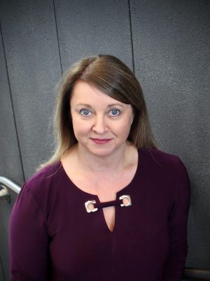Valerie Howe wears a burgundy sweater and looks up at the camera with a gray wall behind her.