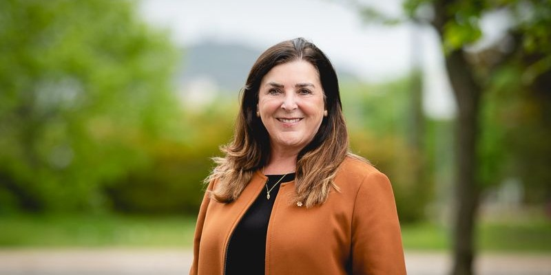 President Vianne Timmons wears a black shirt and brown blazer and stands in front of a green space.